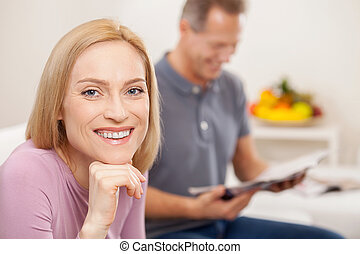 Happy wife. Cheerful mature woman holding hand on chin and smiling while smiling man sitting on background and reading magazine
