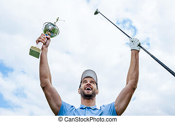 Happy winner. Low angle view of young happy golfer holding driver and trophy while raising his arms with blue sky as background