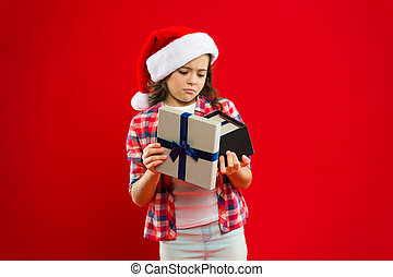 Happy winter holidays. Small serious girl. Present for Xmas. Childhood. Christmas shopping. Little girl child in santa red hat. New year party. Santa claus kid. Great gift