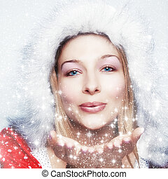 Happy winter woman blowing snowflakes
