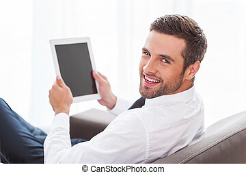 Happy with his new gadget. Rear view of confident young businessman in shirt and tie holding digital tablet and smiling while sitting at the chair