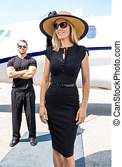 Happy Woman Against Bodyguard And Private Jet