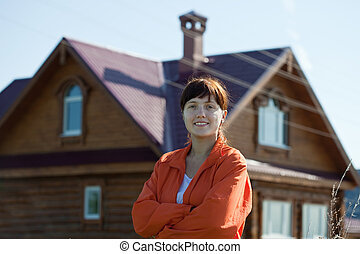 Happy   woman  against her home