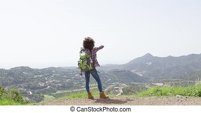 Happy woman against mountains - Back view of female tourist...