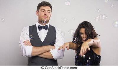 happy woman and bored man at party with bubbles - party, fun...