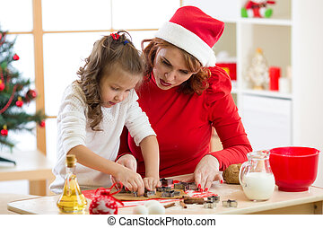 Happy woman and child girl cutting the christmas cookies out of dough together