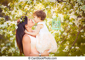Happy woman and child in the blooming spring garden. Child kissing woman. Mothers day holiday concept