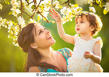 Happy woman and child in the blooming spring garden.Child...