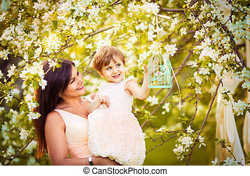 Happy woman and child in the blooming spring garden.Mothers...