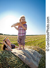 Happy woman and child in wheat field