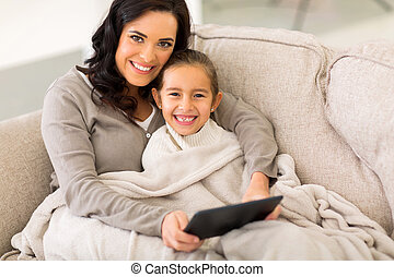 woman and her little daughter snuggle on couch
