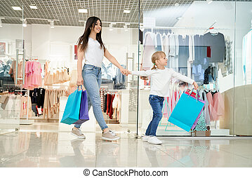 Happy woman and little daughter going out from store in mall