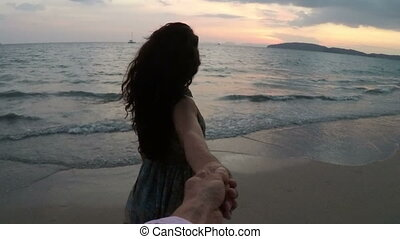 Happy Woman And Man Holding Hands Walking On Beach At Sunset...