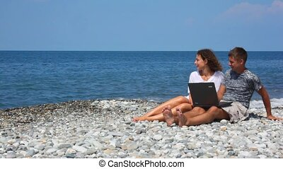 happy woman and man with notebook sitting in rocky beach
