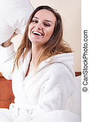 Happy woman and pillow figh - Happy woman in white bathrobe...