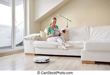 happy woman and robot vacuum cleaner at home - people,...
