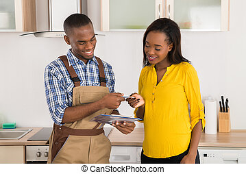 Happy Woman And Serviceman With Clipboard - Young Happy...