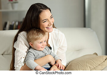 Happy woman and son looking away at home