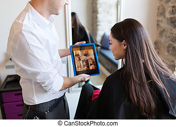 happy woman and stylist with tablet pc at salon - beauty,...