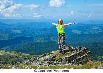 happy woman at mountain peak