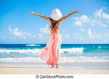 Relaxing beach vacation. Happy woman enjoying sunny day at the beach. Open arms, freedom, happiness and bliss.