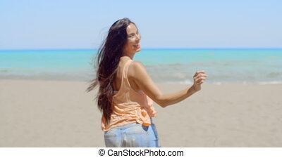 Happy Woman at the Beach Waving at the Camera