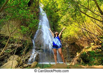 Happy woman at waterfall
