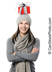 Happy woman balancing a Christmas gift on her head
