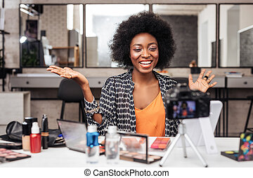 Beautiful african american woman with bright lipstick laughing happily