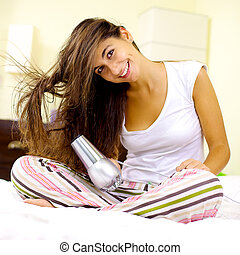 Happy woman blow drying long hair at home
