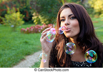 Happy woman blowing soap bubbles