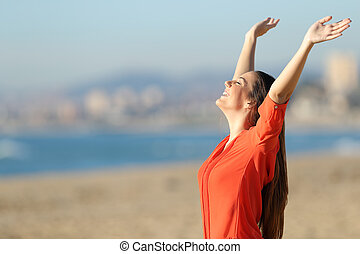 Happy woman breathing and raising arms on the beach - Side...