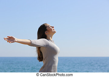 Happy woman breathing deep fresh air and raising arms on the...