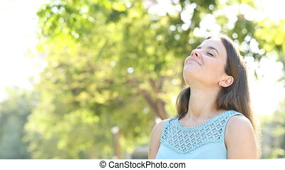 Happy woman breathing deeply fresh air in a forest
