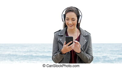 Happy woman browsing and listening to music - Front view of...