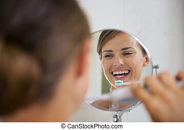 Happy woman brushing teeth with electric toothbrush
