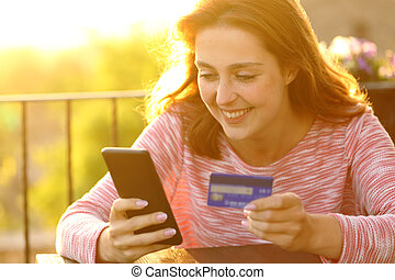 Happy woman buying online with credit card in a balcony