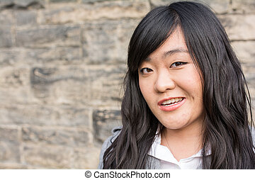 Portrait of attractive young girl in front of a wall with a weird smirk on her face