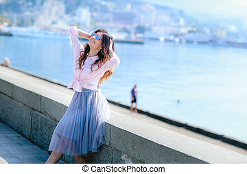 Happy woman by posing near the sea in a hot summer day.