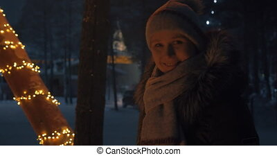 Happy woman by the fire in winter evening
