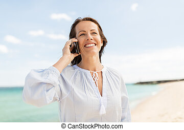 happy woman calling on smartphone at summer beach