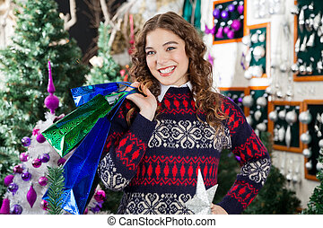 Happy Woman Carrying Shopping Bags In Store