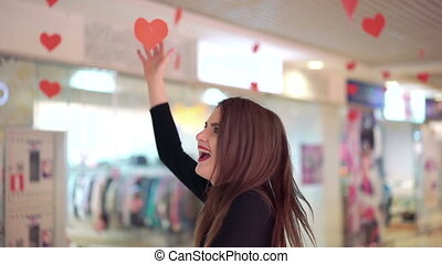 Happy woman catching red hearts, smiling and posing for the camera