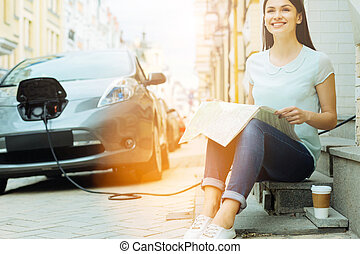 Happy woman charging her electric car and reading a newspaper
