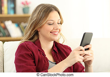 Happy woman chatting on a smart phone at home