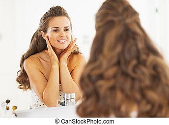 Happy woman checking facial skin condition in bathroom