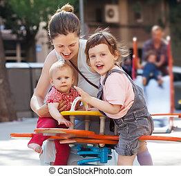 Happy woman children on swings