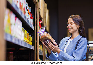 happy woman choosing and buying food in market - sale,...