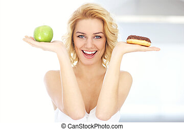 Happy woman choosing between donut and apple
