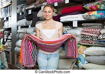 Happy woman choosing blanket